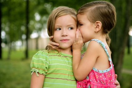 Two twin little sister girls whisper in ear
